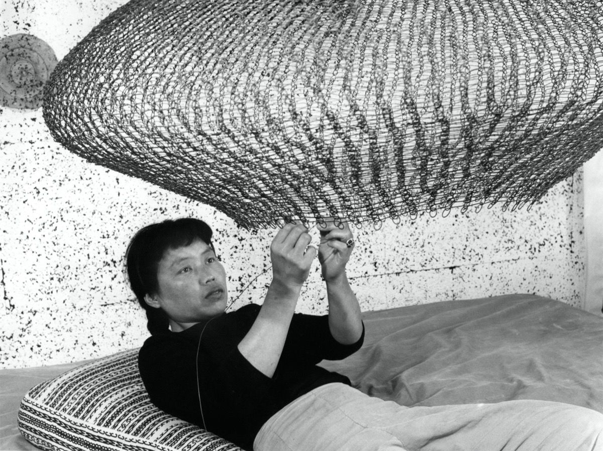 Portrait of Ruth Asawa forming a looped-wire sculpture 1957